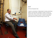 Arif, a mincab driver awaits his next job in a cab office in west London. He's entertaining himself and a friend with a game of cards.