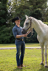 cowboy standing with a horse outdoors