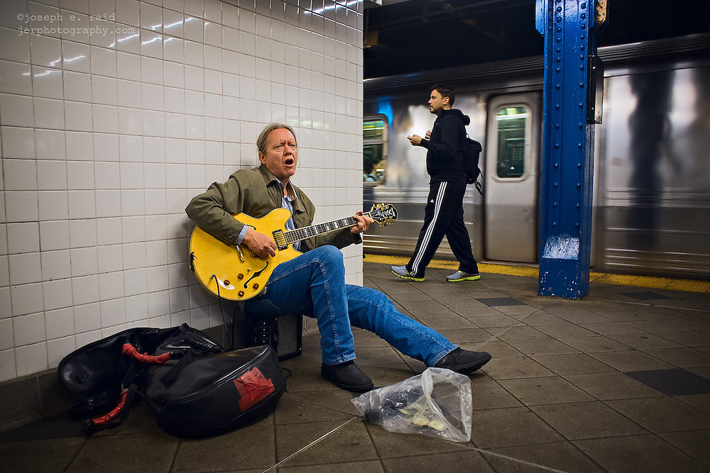Busker playing guitar on 59th Street A/C platform, New York, NY, US