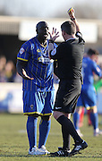 Wimbledon striker ADEBAYO AKINFENWA yellow card during the Sky Bet League 2 match between AFC Wimbledon and York City at the Cherry Red Records Stadium, Kingston, England on 7 March 2015.
