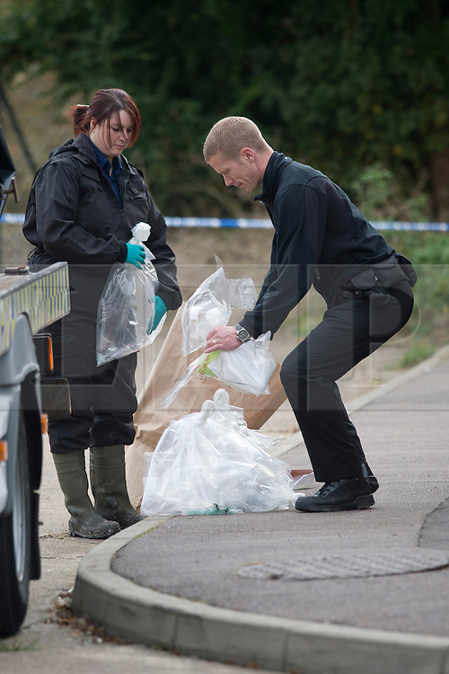 ©  London News Pictures. 15/10/2012. Harlow, UK. A fire investigation team bagging evidence outside a property  on Barn Mead, Harlow, Essex where three children and a woman have died and three others are in hospital following a house fire. Two boys aged 13 and six, a girl aged 11 and the woman were declared dead at the scene. A nine-year-old boy and a three-year-old girl have serious burns and a man has minor burns. Photo credit : Ben Cawthra/LNP