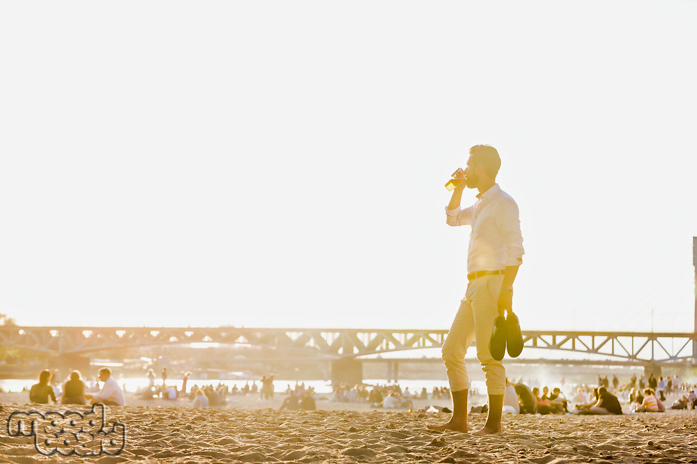 Portrait of young attractive businessman drinking beer and walking barefoot on the beach while holding his shoes
