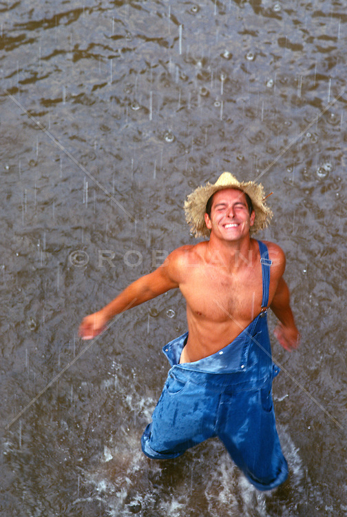 man in overalls enjoying a rain shower while standing in a