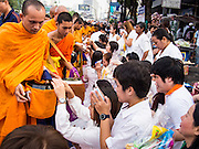 08 SEPTEMBER 2013 - BANGKOK, THAILAND: People make merit by donating alms to a Buddhist monk during a mass giving ceremony in Bangkok Sunday. 10,000 Buddhist monks participated in a mass alms giving ceremony on Rajadamri Road in front of Central World shopping mall in Bangkok. The alms giving was to benefit disaster victims in Thailand and assist Buddhist temples in the insurgency wracked southern provinces of Thailand.      PHOTO BY JACK KURTZ