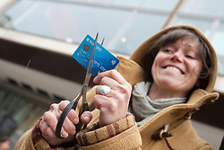 © licensed to London News Pictures. London, UK 27/04/2012. Sara Petrai cuts her Barclays debit cards outside Royal Festival Hall to protest against Barclays AGM today (27/04/12). Photo credit: Tolga Akmen/LNP