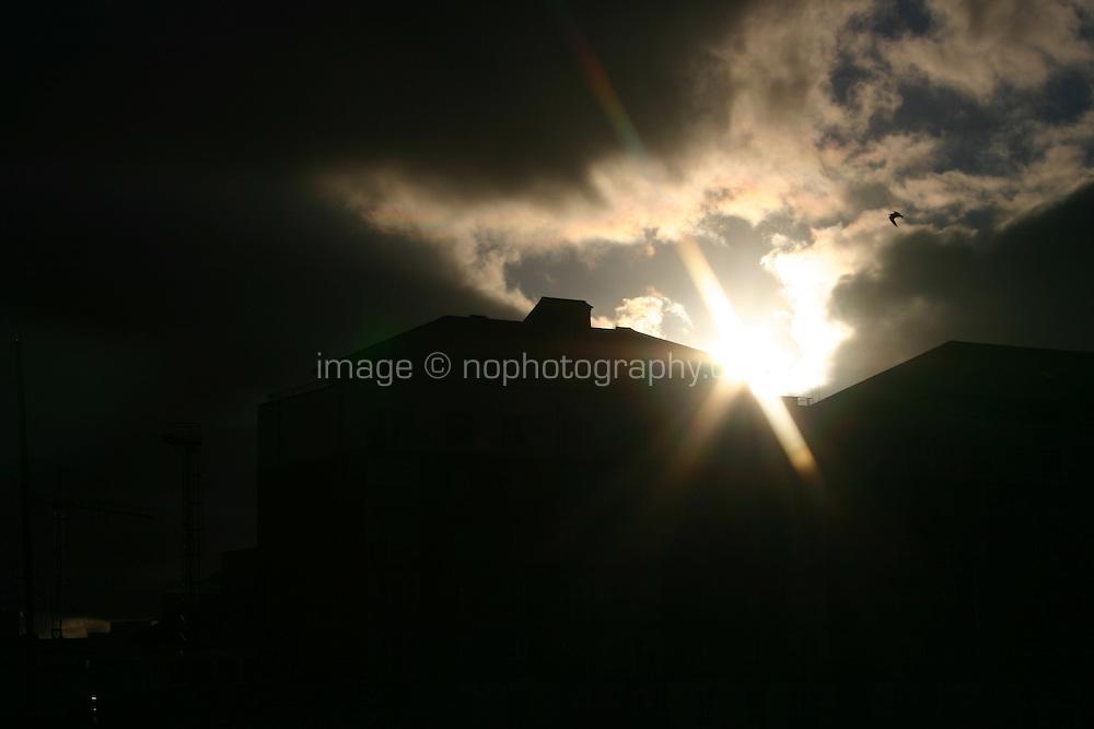 Sunlight against silhouette of buildings