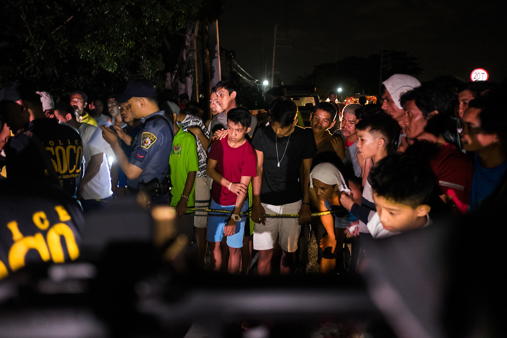 People watch the police while recovering the body of a vicitim on the edge of the street.