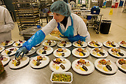 "A lady employee of the world's largest independent provider of airline catering and provisioning services, Gate Gourmet, reaches out to add the last items in the company's factory on the southern perimeter road at Heathrow Airport, West London. Gate Gourmet serve more than 200 million meals on 2 million airline flights a year to their 250-plus airline customers at more than 100 airport locations around the globe. Apart from creating the bespoke meals for an airline's culture and ethnic demands, that pack the pre-flight carts, deliver and load into the aircraft galleys and afterwards, they dispose of the waste and strip, wash and sterilize the equipment. From writer Alain de Botton's book project ""A Week at the Airport: A Heathrow Diary"" (2009). ."