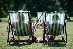 © Licensed to London News Pictures. 22/08/2015. London, UK. The silhouettes of two women sitting on deckchairs in Green Park. Photo credit: Pete Maclaine/LNP