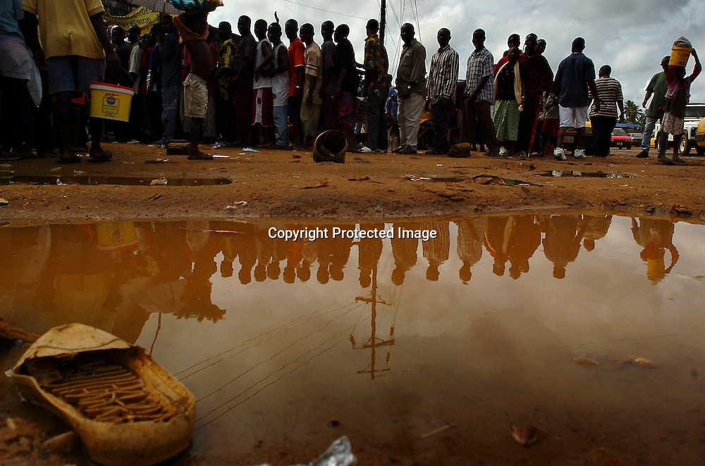 Liberian voters are reflected in a mud puddle as they wait to cast their ballots at a polling station near the Free Port of Monrovia, Liberia, October 11, 2005.  Liberians are choosing a successor to deposed warlord-turned-president Charles Taylor, who was sent into exile in 2003.