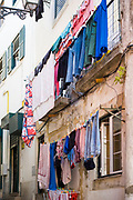 Typical Portugese steep street scene, laundry hanging to dry on washing lines in narrow alleyway in Alfama District, Lisbon, Portugal