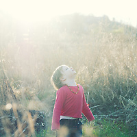A young girl in a field looking up into the sun