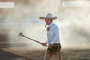 Luis Alfonso Franco stands in a cloud of steam after branding a steer during Team Roping at the family Charreria practice session in the Jalisco Highlands town of Capilla de Guadalupe, Mexico.