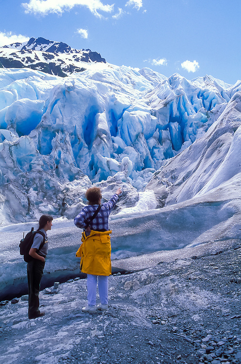 A ranger and tourist enjoying the beauty of Exit Glacier. It is one of few that hikers can easily hike to in Alaska.