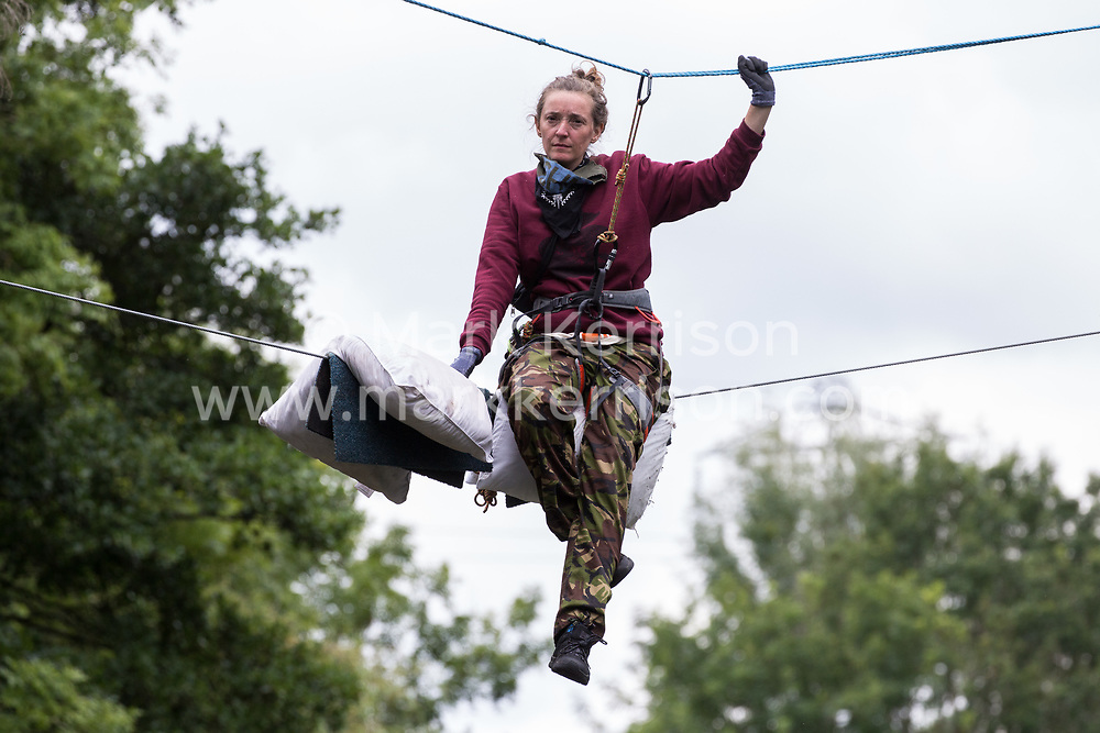 Denham, UK. 24 July, 2020. Swan, an environmental activist from HS2 Rebellion, sits on a line above the shallow river Colne attached behind to an ancient alder tree to try to protect it from destruction in connection with works for the HS2 high-speed rail link in Denham Country Park. She remained on the line for almost fourteen hours before her safety line was cut during a policing operation involving the Metropolitan Police, Thames Valley Police, City of London Police and Hampshire Police.