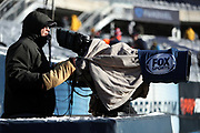 A television cameraman has a heat blanket over his field level TV camera on a cold weather day before the Chicago Bears 2016 NFL week 15 regular season football game against the Green Bay Packers on Sunday, Dec. 18, 2016 in Chicago. The Packers won the game 30-27. (©Paul Anthony Spinelli)
