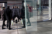 Humerous reflection in plate glass of pedestrians walking through a shopping complex in the financial City of London.