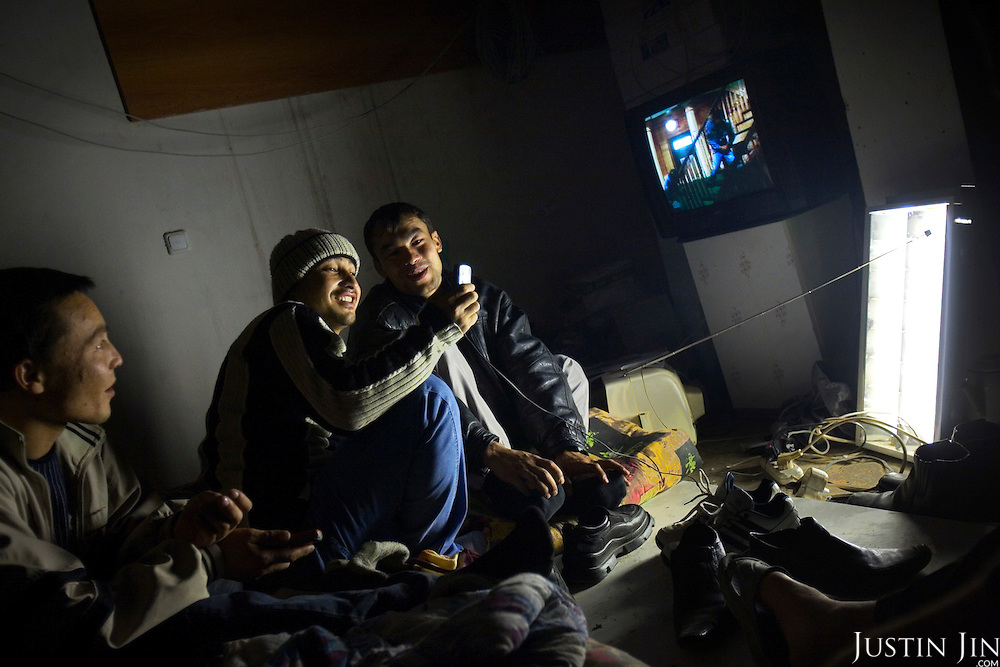 Migrant workers from Uzbekistan look at a mobile phone in a cellar in Moscow. Eleven people cram into the space. Russia is clamping down on unregistered migrant workers.