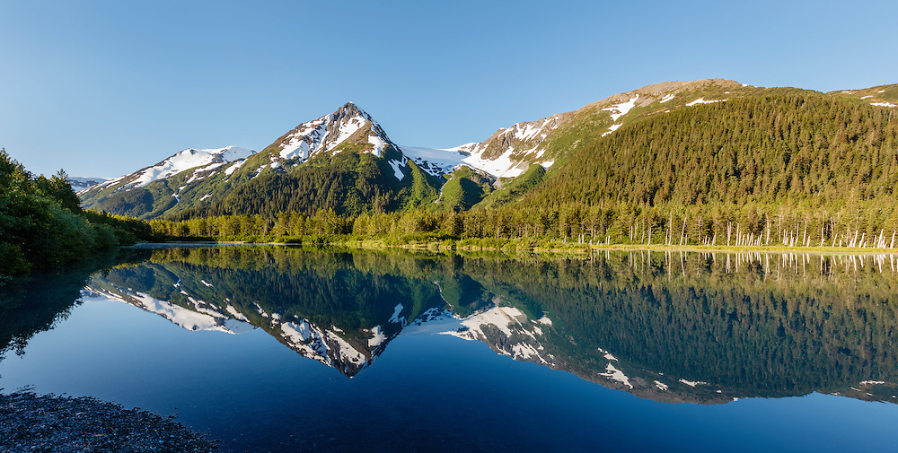 Explorer Glacier is reflected in Explorer Pond in the Chugach National Forest in Portage Valley in Southcentral Alaska. Spring. Morning.