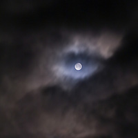A full moon seen through dense clouds