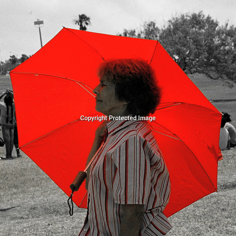 "Lady seeks protection from searing summer sun under her red umbrella in Corpus Christi, Texas. Rendered in B&W color pop. NOTE: Click ""Shopping Cart"" icon for available sizes and prices. If a ""Purchase this image"" screen opens, click arrow on it. Doing so does not constitute making a purchase. To purchase, additional steps are required."