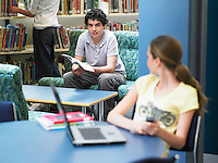 Teenage girl looking at boy sitting in library