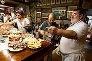 SAN SEBASTIAN - SPAIN - 23 JULY 2010 -- A man sells lotto coupons passes while locals and tourists order and eat tapas, or in Basques called pintxos, for lunch time at the Casa Alcalde Tapas Bar, San Sebastian. PHOTO: ERIK LUNTANG / INSPIRIT Photo.