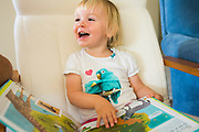 Happy 2 year old girl reading a book on her own