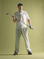 Golfer standing holding club