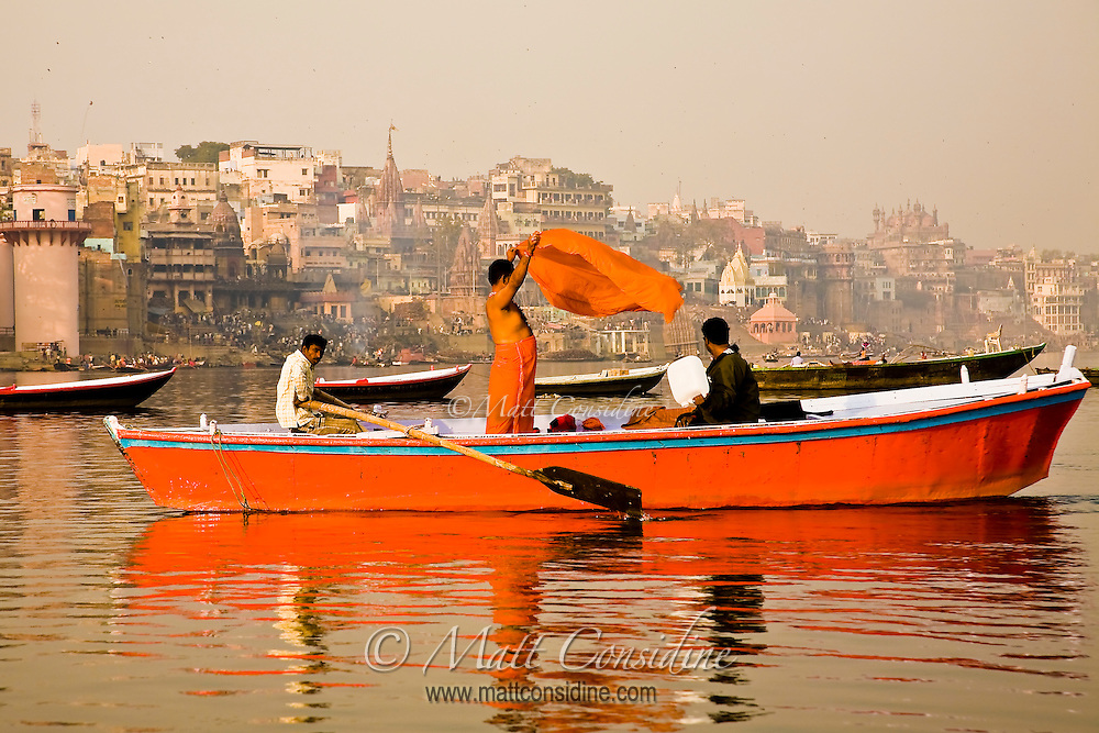 Man airing orange robes after a ritual dip in the Ganges.<br /> (Photo by Matt Considine - Images of Asia Collection)