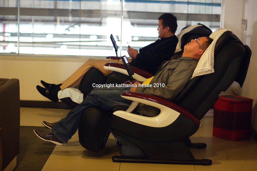 BEIJING, APRIL-22, 2010:   customers relax in a massage chair while waiting for their cars at the BMW dealership .