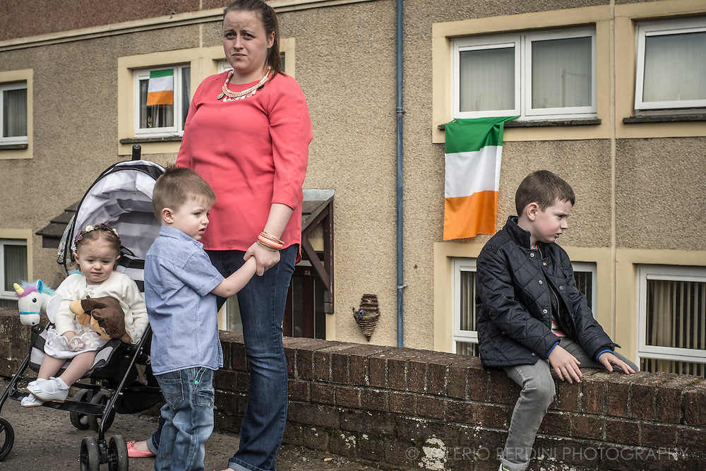 A mother with her three children stands in a working class, catholic neighbourhood of Derry. Irish flags hang from the building to claim belonging.