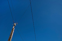 Low angle view of electric wires against clear blue sky