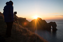 © Licensed to London News Pictures. 05/11/2016. Lulworth, UK.  A photographer captures the sunrise at Durdle Door on the Jurassic Coast in Dorset this morning, 5th November 2016.  Photo credit: Rob Arnold/LNP
