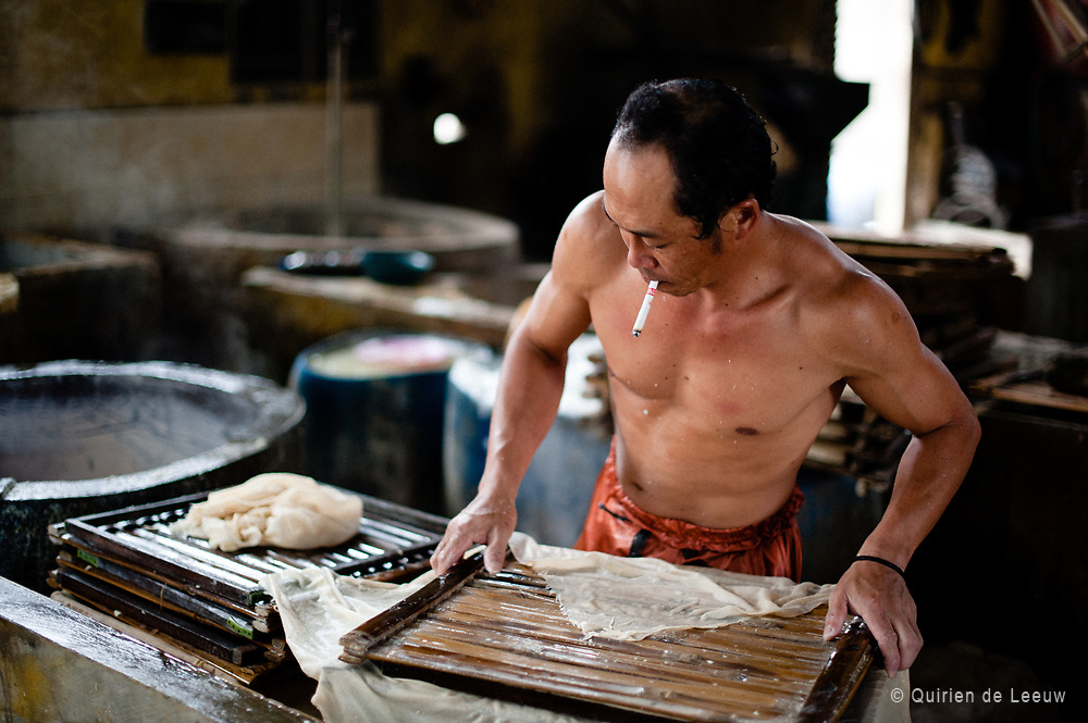 A factory-worker is pressing curds into soft white blocks. <br />