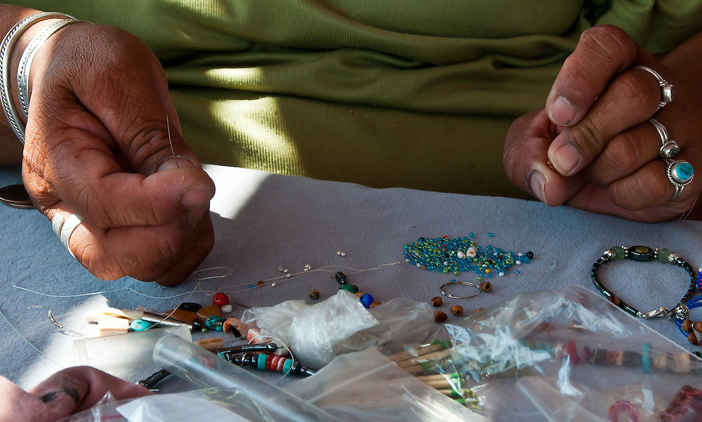 Detailed view of a Navajo women making necklaces for the visiting tourists.  Monument Valley, Utah