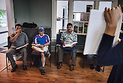 Sergio Martinez, left, Mike Miguel Andrade, and Palo Ruiz, all temporary workers, listen to Rose Davies, a student intern, during an English class at Agricultural Workers Alliance Support Centre in uptown Leamington.