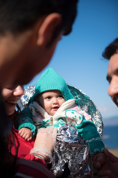 Ala, 10 months old and from Qamishli, Syria, is held by volunteers who greeted her and her family when they reached the coast of Lesbos at the end of the dangerous journey from Turkey. The family is Kurdish.