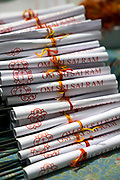 PUTTARPATHI, INDIA - 01st November 2019 - Om Sri Sai Ram prayer paper tied into rolls with incense sticks for people to write fortune blessings at a shrine in Puttarpathi, Andhra Pradesh, South India