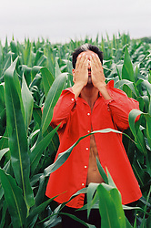 Man in an orange shirt covering his eyes while standing in a corn field