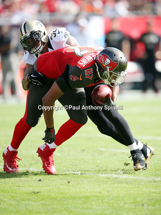 Tampa Bay Buccaneers tight end Austin Seferian-Jenkins (87) gets tackled by New Orleans Saints strong safety Kenny Vaccaro (32) after catching a first quarter pass for a gain of 13 yards and a first down during the 2015 week 14 regular season NFL football game against the New Orleans Saints on Sunday, Dec. 13, 2015 in Tampa, Fla. The Saints won the game 24-17. (©Paul Anthony Spinelli)