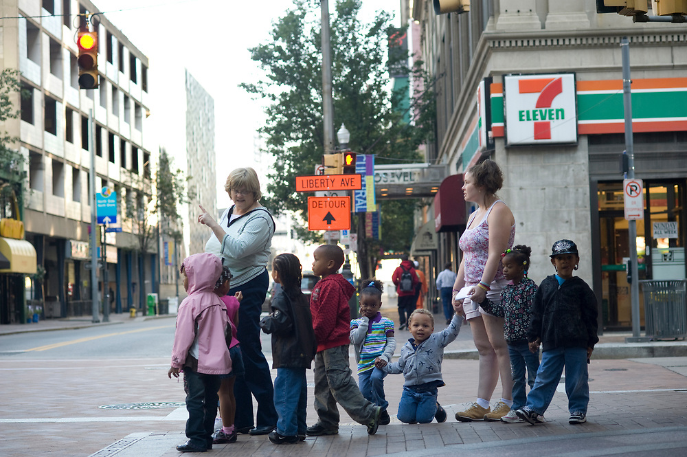 Director Lynne Geidel points out a building to her preschool students from Small World 2 Early Learning & Development Center before crossing 6th Street while taking a walk in downtown Pittsburgh. She is joined by an assistant Michelle Gabig (right).