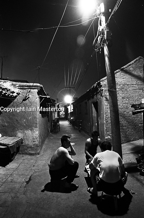 Men playing chess by streetlight at night in a hutong in Beijing China