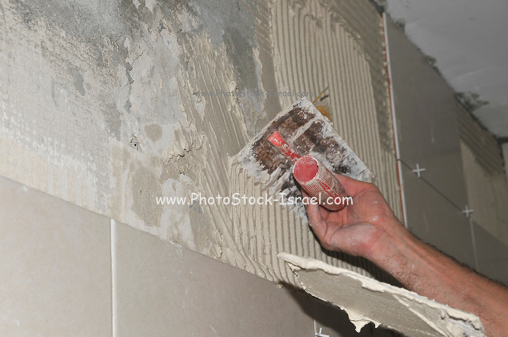 Plasterer sticking tiles to a bathroom wall