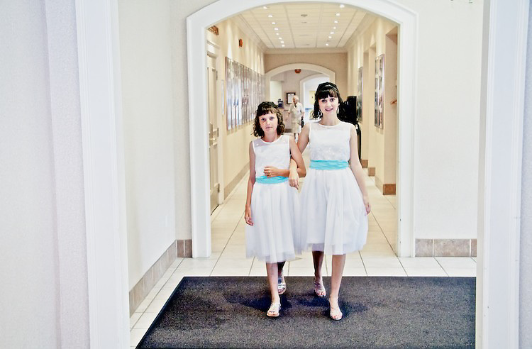 The flower girls make their way down the hotel hallway to the wedding reception. <br /> <br /> To view Katie and Brad's complete Wedding Gallery Collection, visit the Client Area and log-in. You'll be able to view all images as a slideshow, order prints and more.<br /> <br /> &copy; Images of a Promise by Dean Oros Photo + Design