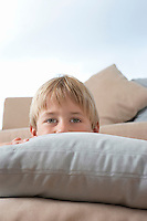 Boy Hiding Behind Pillows