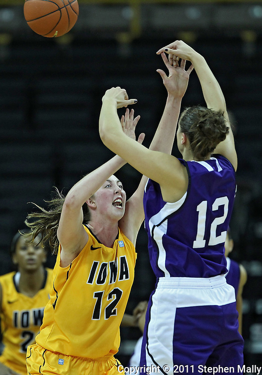December 30, 2011: Northwestern Wildcats guard Allison Mocchi (12) passes over Iowa Hawkeyes center Morgan Johnson (12) during the NCAA women's basketball game between the Northwestern Wildcats and the Iowa Hawkeyes at Carver-Hawkeye Arena in Iowa City, Iowa on Wednesday, December 30, 2011.