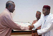 16635African Leadership Day: Photos by Colby Ware..9/24/04--Dr. Dauda Abubakar, professor in the Department of Political Science, accepts a handmade beadwork replica of Africa from Alhaji Bashir Albishir Bukar, Emir of Machina, Yobe State, Nigeria and Mohammed Kati Machina (background) at the African Leadership Day Conference in Bentley Hall. Dr. Abubakar was awarded the craftwork on behalf of the African Future Leaders Forum.