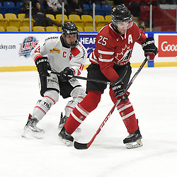 WHITBY, - Dec 13, 2015 -  WJAC Game 2- Team Switzerland vs Team Canada East at the 2015 World Junior A Challenge at the Iroquois Park Recreation Complex, ON. Livio Stadler #14 of Team Switzerland battles for control with Maxime St. Pierre #25 of Team Canada East during the first period. (Photo: Andy Corneau / OJHL Images)