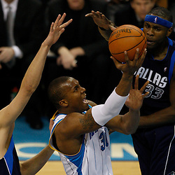Mar 22, 2010; New Orleans, LA, USA; New Orleans Hornets forward David West (30) shoots between Dallas Mavericks defenders Dirk Nowitzki (41) and Brendan Haywood (33) during the second half at the New Orleans Arena. Mandatory Credit: Derick E. Hingle-US PRESSWIRE